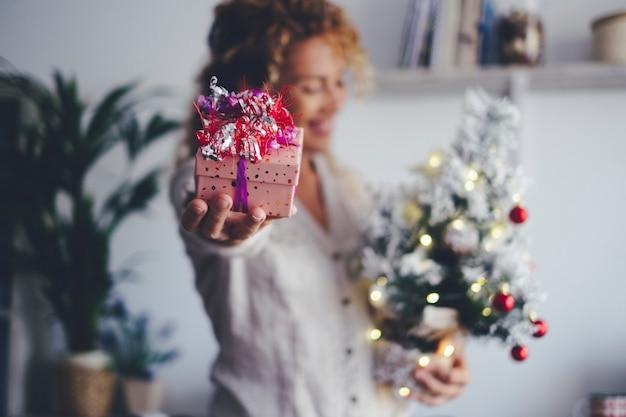 Gros plan sur un cadeau de noël et une femme heureuse défocalisée tenant un arbre et une décoration à la maison pendant les fêtes de fin d'année. concept d'échange de cadeaux et de personnes