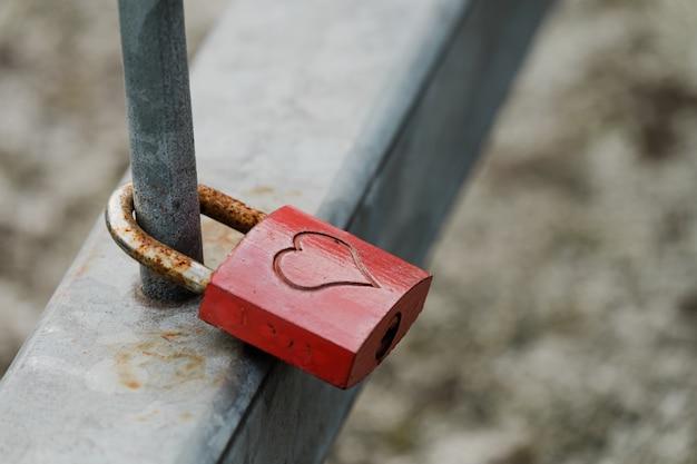 Gros plan d'un cadenas en métal avec un cœur suspendu à une clôture