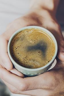Gros plan d'un café expresso savoureux avec une mousse jaune savoureuse dans une tasse en céramique verte. main mâle tenant une boisson chaude chaude. toning.