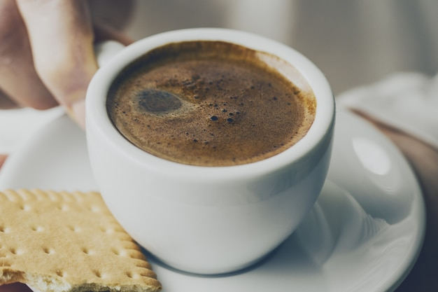 Gros plan d'un café expresso savoureux avec de la mousse savoureuse dans une petite tasse en céramique. main femelle tenant une boisson chaude chaude.