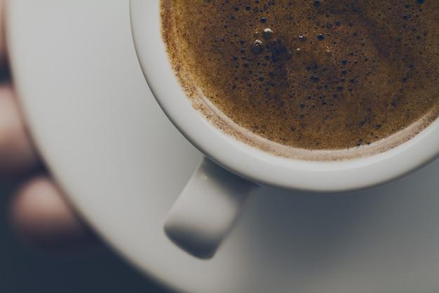 Gros plan d'un café expresso savoureux avec de la mousse savoureuse dans une petite tasse en céramique. main mâle tenant une boisson chaude chaude.