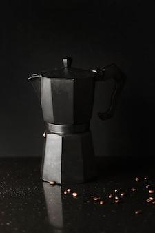 Gros plan d'une cafetière avec des grains de café torréfiés sur fond noir