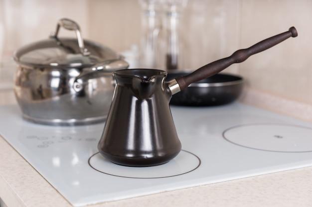 Gros plan de la cafetière turque traditionnelle sur le dessus de la cuisinière dans la cuisine avec casseroles et poêles