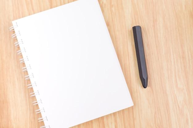 Gros plan cahier à anneaux ouvert vide avec un crayon noir sur la table en bois