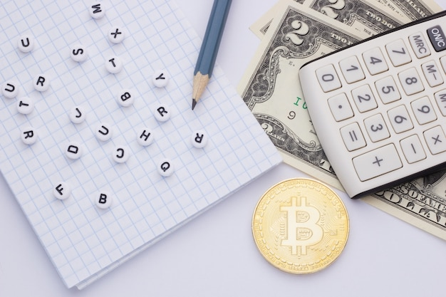 Gros plan, sur une calculatrice à fond blanc, de l'argent (bitcoin) et un bloc-notes avec des lettres