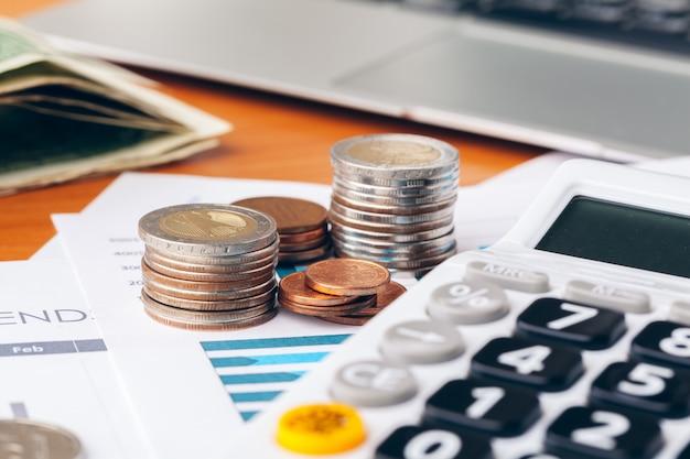 Gros plan d'une calculatrice et de pièces de monnaie sur un fond d'affaires