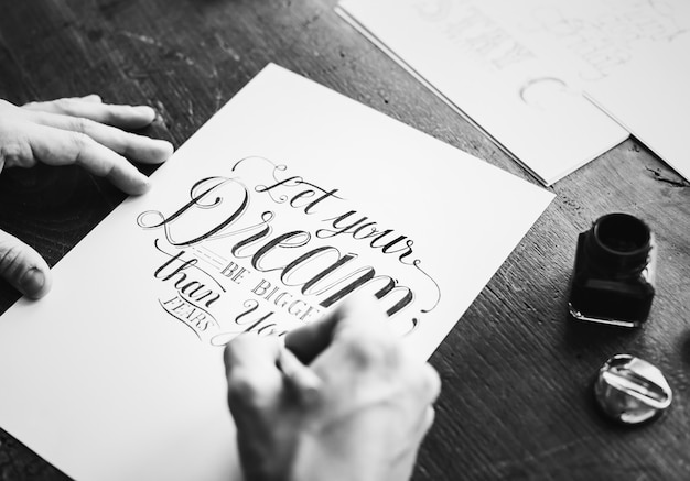 Gros plan d'un calligraphe travaillant sur un projet