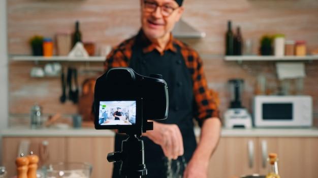 Gros plan sur une caméra diffusant un podcast culinaire en direct. chef influenceur blogueur à la retraite utilisant la technologie internet pour communiquer, bloguer sur les réseaux sociaux avec un équipement numérique
