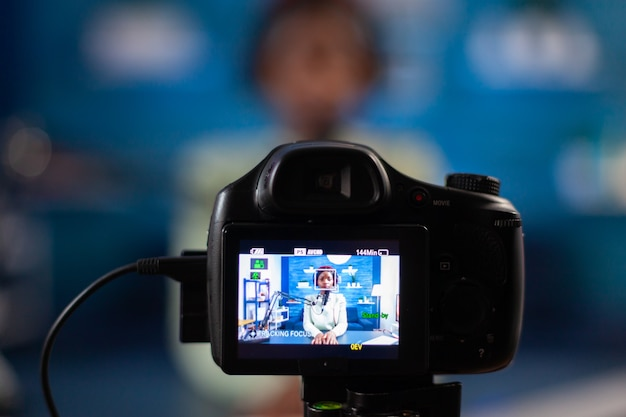 Gros plan sur une caméra professionnelle assise devant une émission en ligne d'enregistrement reflex numérique. s'exprimant lors d'une diffusion en direct, un blogueur discutant dans un podcast avec des écouteurs.