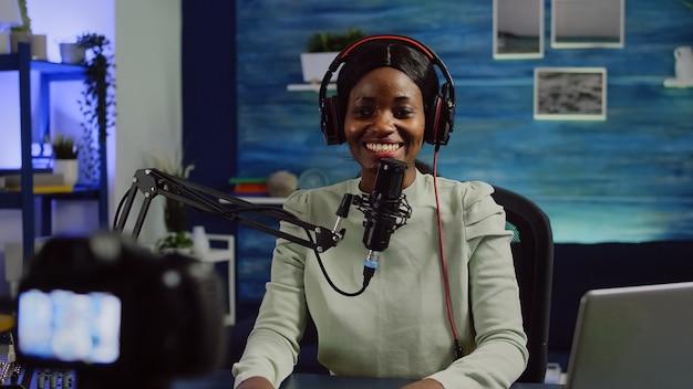 Gros plan sur une caméra vidéo enregistrant un influenceur africain en train de parler pendant un podcast en ligne