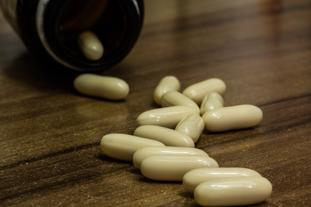 Gros plan de capsules de médecine blanche sur une surface en bois