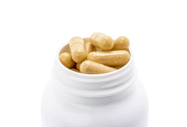 Gros plan sur des capsules de suppléments à base de plantes brunes pour la santé à l'intérieur d'une bouteille en plastique blanche isolée sur fond blanc