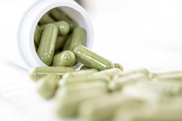 Gros plan de capsules vertes médicaments à base de plantes débordant de la bouteille