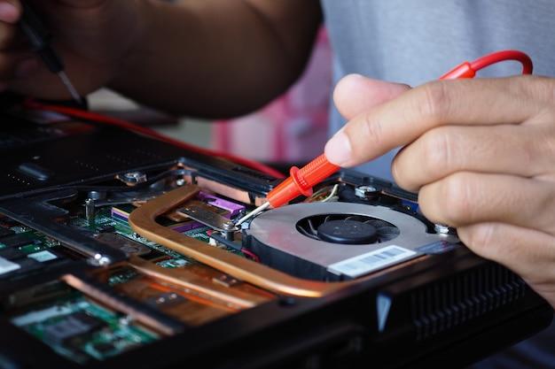 Gros plan d'une carte de circuit imprimé main technicien masculin avec multimètre numérique