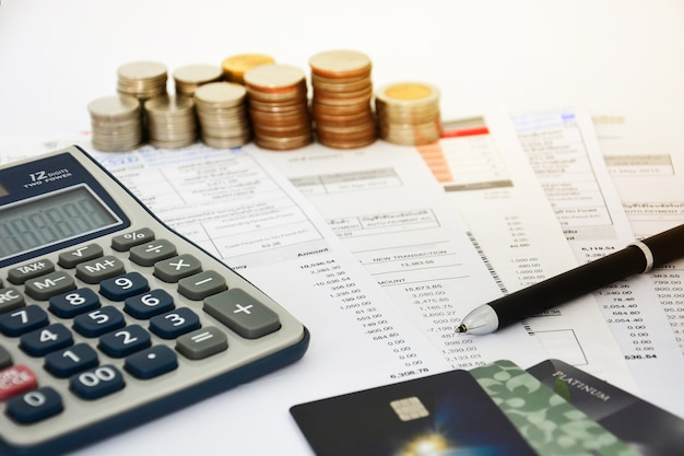 Gros plan d'une carte de crédit avec relevés de carte de crédit, pièces de monnaie et calculatrice