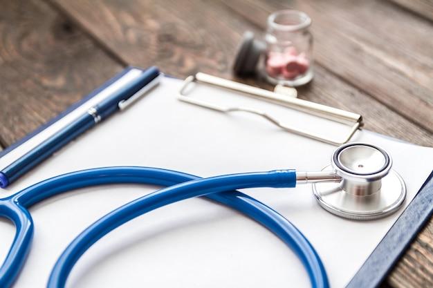 Gros plan sur la carte médicale du patient, un stéthoscope et des pilules sur le bureau du médecin