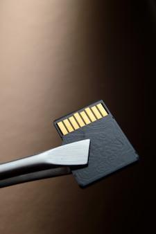 Gros plan sur une carte mémoire micro sd sur un fond dégradé doré, serré avec une pince à épiler.