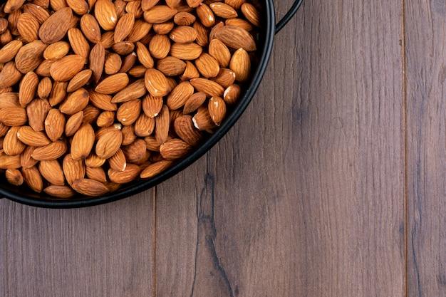 Gros plan d'une casserole d'amande sur une table en bois. horizontal