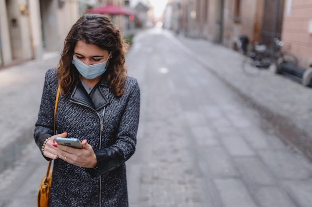 Gros plan caucasien souriant jeune femme marchant dans un centre-ville à l'aide de smartphone pendant la saison froide de l'hiver.