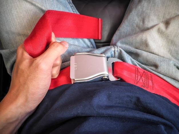 Gros plan des ceintures de sécurité de l'homme sur le siège de l'avion.