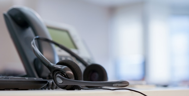 Gros plan sur le centre d'appel casque avec téléphone au bureau concept de salle d'opération de surveillance