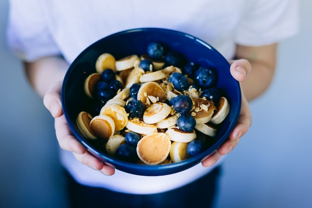 Gros plan de céréales mini pancake, mini crêpes dans un bol bleu foncé avec du miel de sirop d'érable et des bleuets dans les mains de l'enfant. contexte alimentaire.