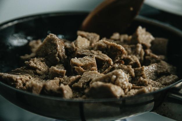 Un gros plan de certains aliments végétaliens de tofu sur la poêle pendant la cuisson