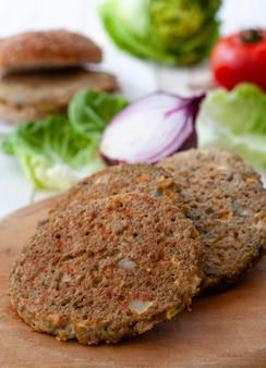 Gros plan certains hamburger de quinoa végétarien sur une base en bois et certains légumes et oeufs fond