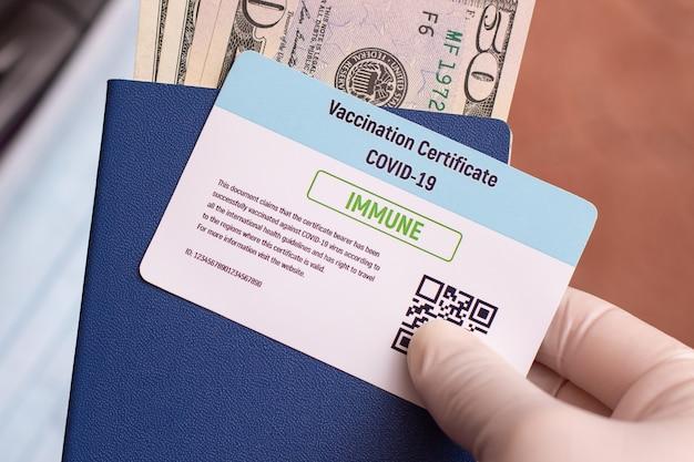 Gros plan d'un certificat de vaccination covid-19, passeport, argent liquide entre les mains d'un voyageur lors de la préparation d'un voyage