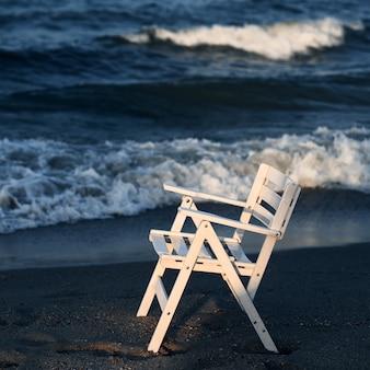 Gros plan d'une chaise en bois blanche sur fond de vagues de la mer.