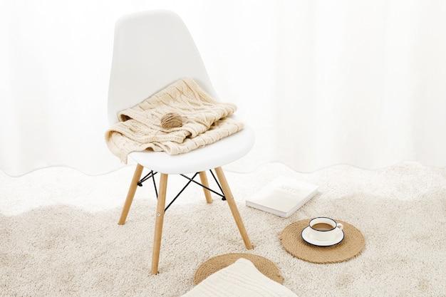 Gros plan d'une chaise avec des couvertures dessus sur un tapis moelleux avec une tasse de café et un bloc-notes dessus