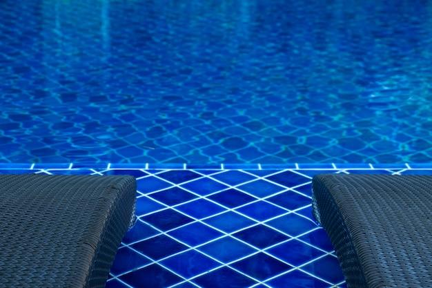 Gros plan d'une chaise de piscine en rotin au bord de la piscine à l'eau bleue