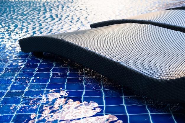 Gros plan d'une chaise de piscine en rotin au bord de la piscine avec le reflet de l'eau bleue et du soleil