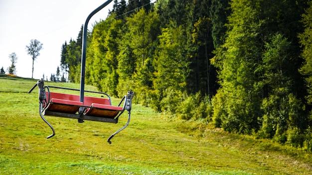 Un gros plan de chaise sur les remontées mécaniques dans les montagnes et les forêts. siège vide de téléphérique parmi les arbres, champ d'herbe dans la forêt verte sur la colline, été ensoleillé