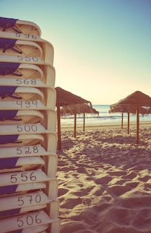 Gros plan sur des chaises de plage empilées et des parasols en bois dans une belle plage vide au coucher du soleil d'été. édition de tons doux et chauds.