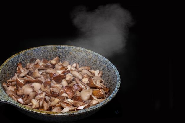 Gros plan de champignons frits ou cuits dans une poêle, la vapeur s'élève des champignons chauds, isolés sur fond noir. concept d'alimentation saine, régime alimentaire végétarien