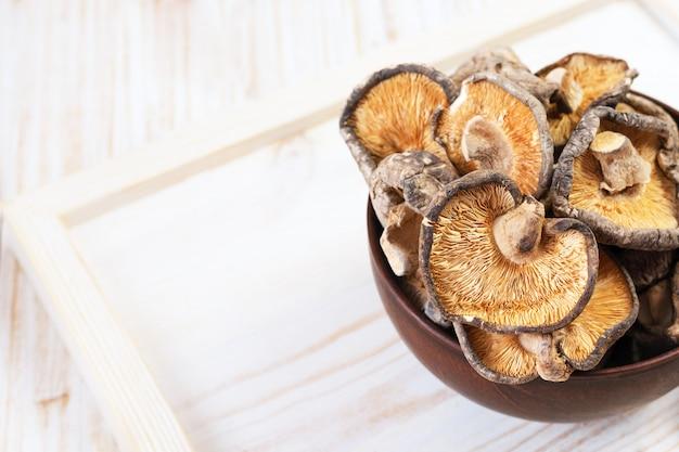 Gros plan de champignons shiitake séchés sur fond de bois