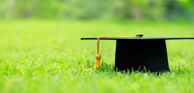 Gros plan chapeau de graduation sur l'herbe verte au printemps dans le parc extérieur