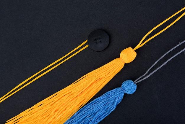 Gros plan chapeau de graduation noir et jaune, bleu gland