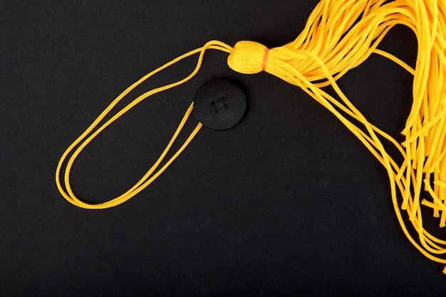 Gros plan chapeau noir de graduation et gland jaune