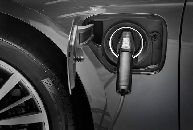 Gros plan de charge de voiture électrique sur un parking avec station de charge de voiture électrique