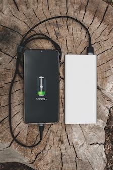 Gros plan des charges de smartphone moderne de la banque d'alimentation portable sur l'ancien concept technologique moderne de souche