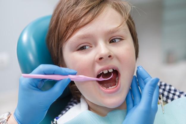 Gros plan d'un charmant jeune garçon obtenant un examen dentaire