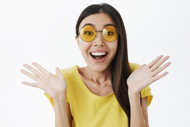 Gros plan d'une charmante femme élégante ravie dans des lunettes de soleil à la mode et t-shirt jaune en agitant les paumes surélevées près des épaules