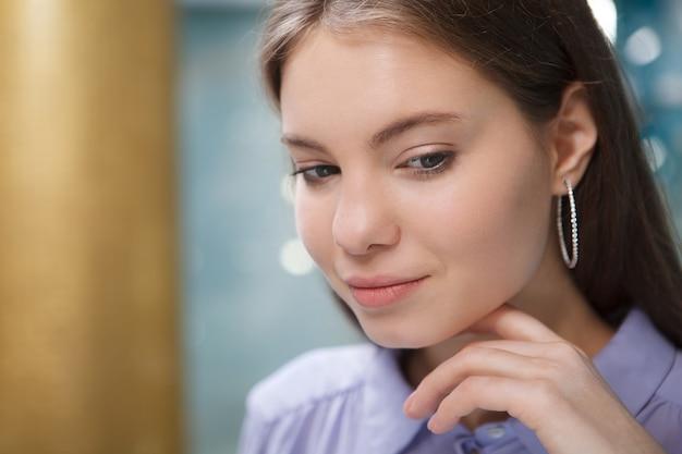 Gros plan d'une charmante femme portant des boucles d'oreilles en diamant