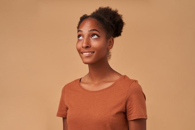 Gros plan d'une charmante jeune femme brune à la peau foncée portant ses cheveux bouclés en noeud tout en posant sur beige avec les mains vers le bas et à la recherche rêveuse