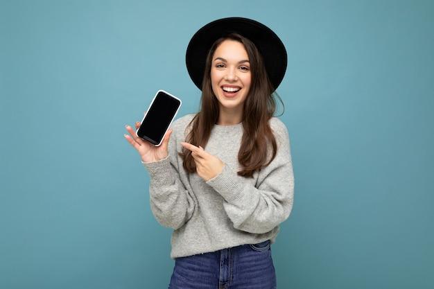 Gros plan de la charmante jeune femme heureuse portant un chapeau noir et pull gris tenant le téléphone regardant la caméra doigt pointé