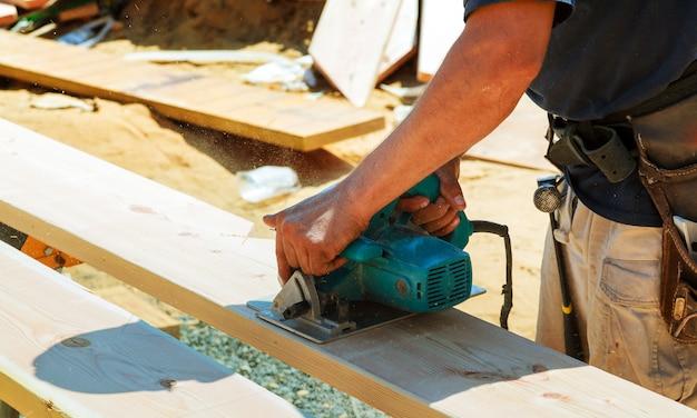 Gros plan d'un charpentier à l'aide d'une scie circulaire pour couper une grande planche de bois