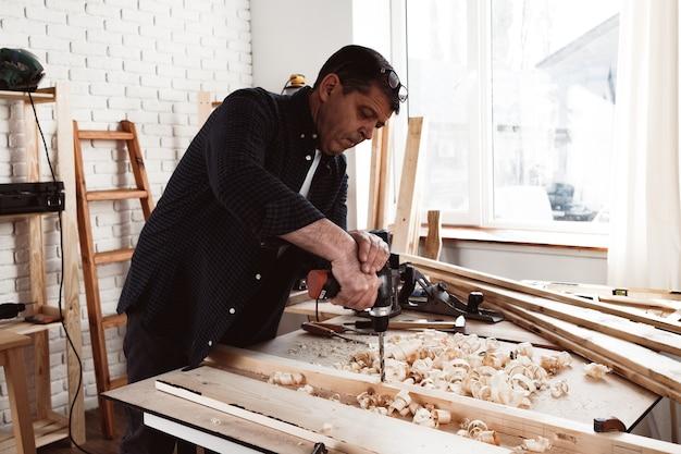 Gros plan d'un charpentier perçant un trou dans le bois