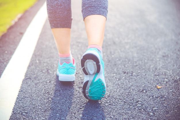 Gros plan sur la chaussure, coureur athlète pieds courir sur route sous la lumière du soleil le matin.